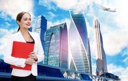 Бизнес-леди с доской сзажимом для бумаги над предпосылкой городского пейзажа стоковые изображения rf