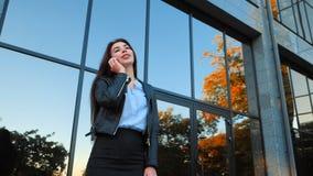 Бизнес-леди с концом смартфона вверх около офисного здания Девушка имеет разговор с сотовым телефоном красивейше сток-видео