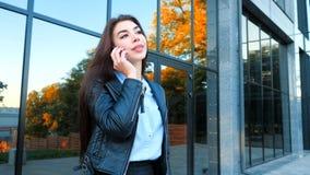 Бизнес-леди с концом смартфона вверх около офисного здания Девушка имеет разговор с сотовым телефоном красивейше акции видеоматериалы