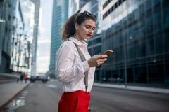 Бизнес-леди с телефоном около офиса стоковое фото