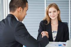 бизнес-леди тряся руки с бизнесменом в офисе смотреть девушки камеры стоковое фото