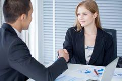 бизнес-леди тряся руки с бизнесменом в офисе стоковое изображение
