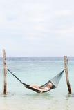 Бикини женщины нося и шляпа Солнця в гамаке пляжа Стоковые Изображения