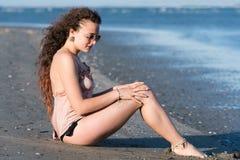 Бикини носки женщины, сидя на пляже Стоковые Фотографии RF