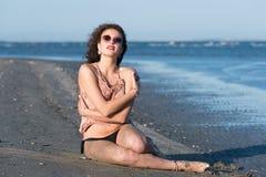 Бикини носки женщины, сидя на пляже Стоковые Изображения RF