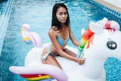 Бикини сексуальной азиатской женщины нося и ослаблять на единороге в бассейне стоковая фотография rf