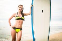 Бикини серфера женщины нося с Surfboard на пляже Стоковая Фотография RF
