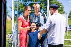 Билеты семьи покупая для круиза реки от лодочника стоковое фото