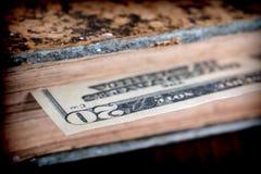 Билл 100 американских долларов спрятанных в старой книге Стоковое Изображение