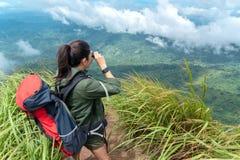 Бинокли взгляда женщины Азии Hiker и стоять на горе Женский рюкзак приключения и располагаться лагерем на походе в на открытом во стоковые изображения