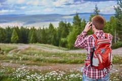 Бинокли мужского путешественника наблюдая в расстояние против леса и облачного неба стоковая фотография