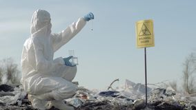 Биологическая опасность, химик Hazmat в защитную одежду беря зараженный образец отброса в пробирке для рассматривать дальше акции видеоматериалы