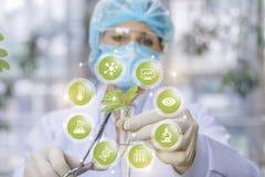 Биолог держит рему с заводом в одной руке и медицинской струбцине в другом за системой значков лаборатории стоковое фото rf