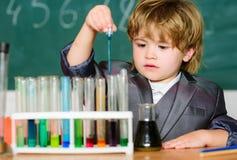 Биотехнология и фармация Зрачок гения o Экспериментировать с химией Талантливый тест мальчика ученого стоковое изображение