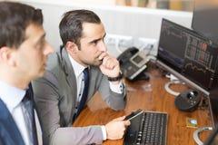 Биржевые маклеры смотря экраны компьютера, торговать онлайн Стоковые Изображения