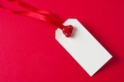 Бирка подарка рождества на красном цвете Стоковое фото RF