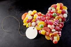 Бирка прикрепленная к сердцу сделанному из много малых конфет Стоковые Изображения RF