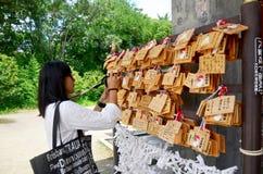 Бирка тайской женщины путешественника смотря и снимая фото Ema деревянная или w Стоковые Фото