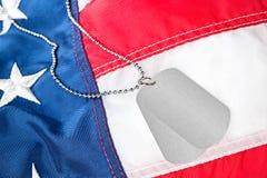 Бирки собаки на американском флаге Стоковая Фотография