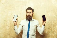 битник или бородатый человек сравнивают мобильный телефон и smartphone стоковая фотография