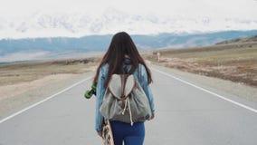 Битник маленькой девочки подростковый идет на шоссе с longboard С рюкзаком лагеря и курткой jersey Против акции видеоматериалы
