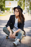 Битник сидя на скейтборде Стоковое Изображение