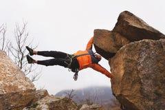 Битник - смертная казнь через повешение альпиниста на одной руке на утесе против фона кавказских гор в последней осени Стоковое Изображение