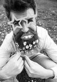 Битник с бородой на жизнерадостной стороне, представляющ с звездой сформировал стекла и губы Гай смотрит славно с цветками маргар стоковые фото