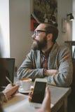 Битник с бородой с smartphone и компьтер-книжкой на таблице уступая Стоковое Изображение