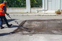 Битумная эмульсия работника дороги распыляя Стоковое Фото