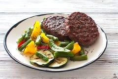 Бифштексы зажаренные с овощами в белой плите Стоковые Изображения