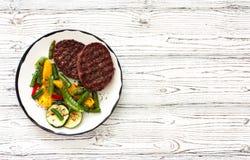 Бифштексы зажаренные с овощами в белой плите Стоковое Изображение RF