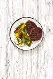 Бифштексы зажарили с овощами в белой плите на белизне сватают Стоковое фото RF