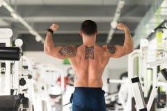 Бицепс фитнеса культуриста модельный представляя двойной после тренировок Стоковые Изображения RF