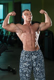 Бицепс фитнеса культуриста модельный представляя двойной после тренировок Стоковое фото RF