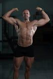 Бицепс фитнеса культуриста модельный представляя двойной после тренировок Стоковая Фотография RF