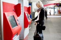 Билет на поезд женщины покупая используя торговый автомат на станции Стоковые Фото