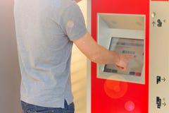 Билет на поезд человека покупая используя торговый автомат на станции стоковое изображение rf