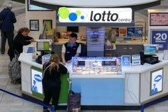 Билет лотереи людей покупая на розничном торговце стоковое фото