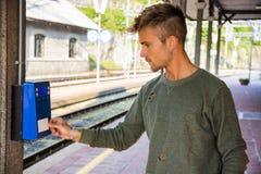Билет человека покупая на станции стоковое изображение