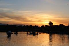 Благоустраивайте заход солнца плавучих домов и Shikara на озере Dal Стоковая Фотография