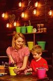 Благоустраивать концепцию Женщина и мальчик пересаживая цветок в новом баке, благоустраивая Крытый благоустраивать Дом стоковые фото