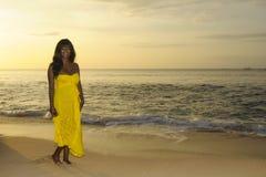 Блестящая Афро-американская чернокожая женщина в шикарном и элегантном платье лета представляя ослабленный идти на пляж захода со стоковое изображение