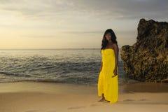 Блестящая Афро-американская чернокожая женщина в шикарном и элегантном платье лета представляя ослабленный идти на пляж захода со стоковое фото rf