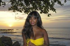 Блестящая Афро-американская чернокожая женщина в шикарный и элегантный представлять платья лета ослабила на пляже захода солнца л стоковое изображение rf