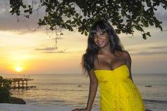 Блестящая Афро-американская чернокожая женщина в шикарный и элегантный представлять платья лета ослабила на пляже захода солнца л стоковое фото rf