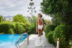 Блестящая, сексуальная и горячая белокурая модельная девушка с совершенным телом, в купальнике, стоит с ей назад около бассейна Стоковое Изображение