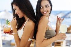 Блестящие девушки выпивая напитки на пляже Стоковое Изображение RF