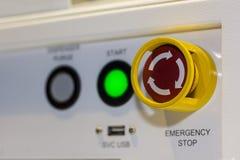 Близкая поднимающая вверх кнопка аварийной остановки на пульте управления машины для безопасности на фабрике стоковое изображение