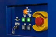 Близкая поднимающая вверх кнопка аварийной остановки на пульте управления машины для безопасности на фабрике стоковые фото